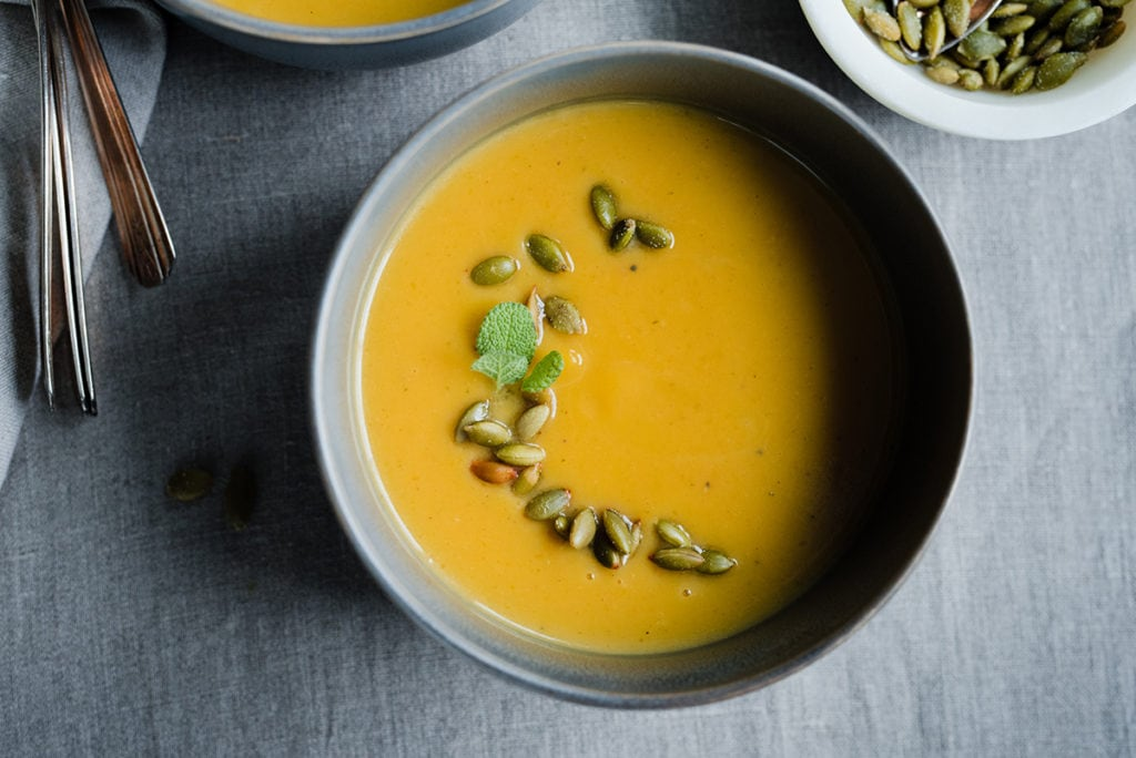 A bowl of paleo pumpkin soup garnished with roasted and salted pumpkin seeds. This healthy pumpkin soup is made with coconut milk, fresh herbs, and seasonal fall spices.