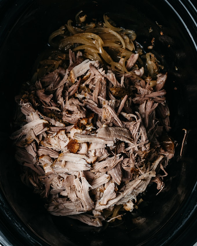 Cooked and shredded apple cider pulled pork in a slow cooker.