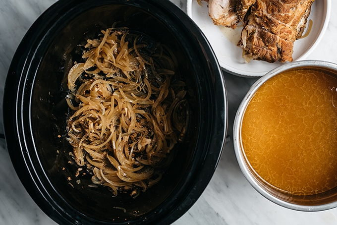 Leftover onions in a dutch oven, with a bowl of apple cider sauce, and a cooked pork shoulder on the side.