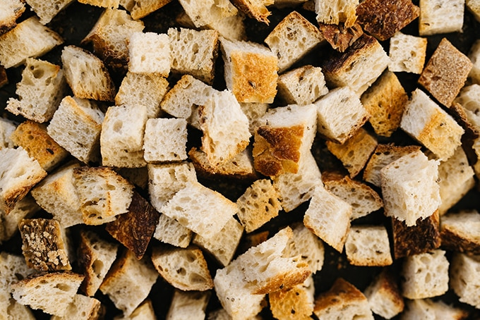 Rye bread croutons on a baking sheet for sausage and cranberry stuffing.