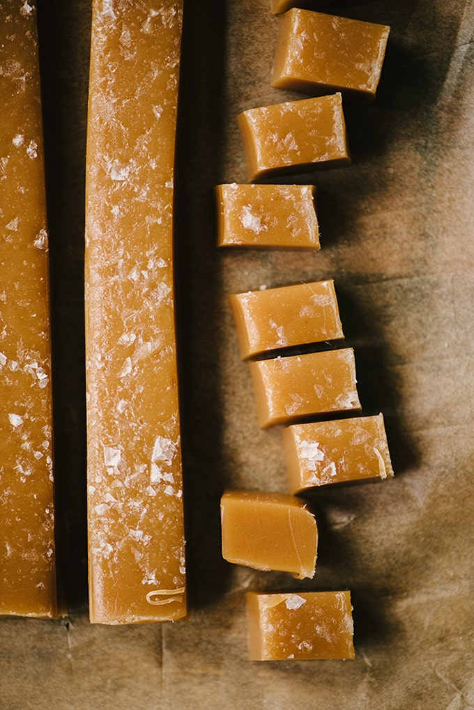 Slices and pieces of homemade salted caramels on a piece of parchment paper.