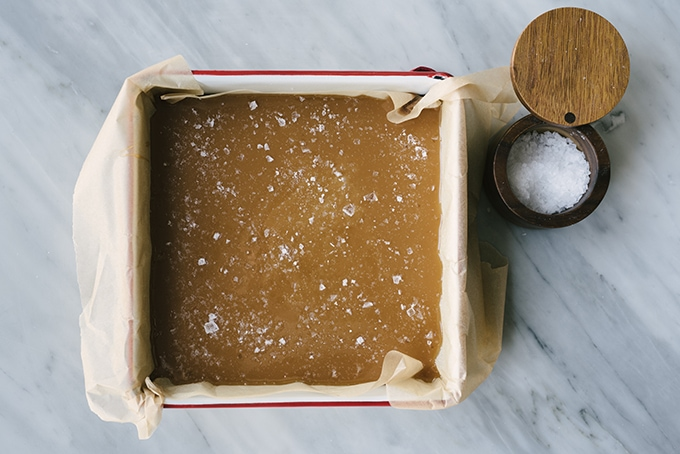 Caramel candy in a parchment lined baking sheet, dusted with flaky maldon sea salt.