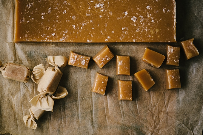 A block of homemade salted caramel candy with small pieces cut off and wrapped in parchment paper.