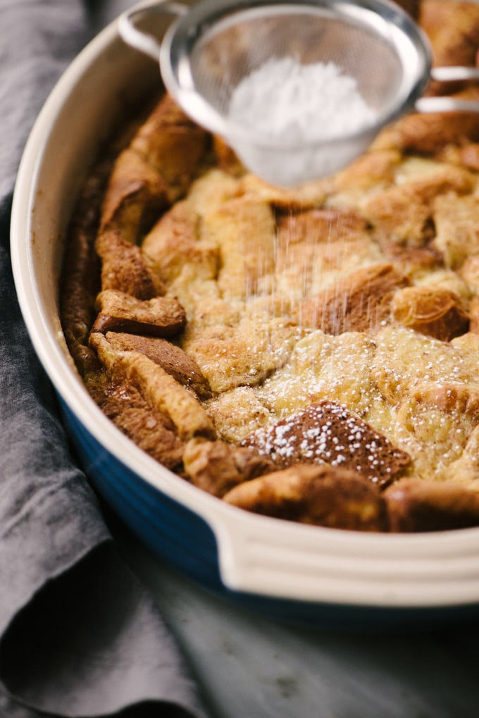Powdered sugar in a small fine mesh sieve being sprinkled over a french toast bread pudding breakfast casserole.