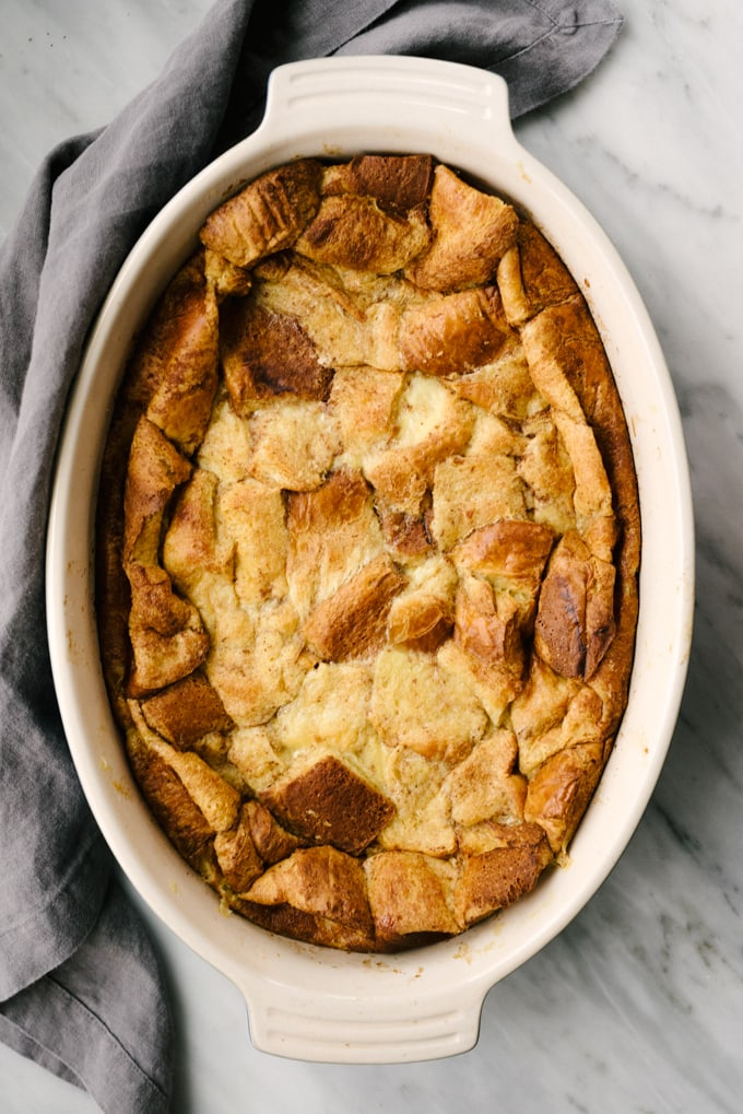 Baked french toast bread pudding in a casserole dish with a grey napkin.