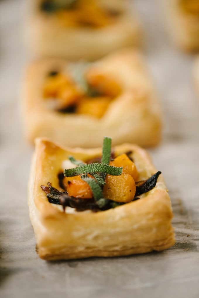 A baked mini butternut squash tart with ricotta cheese, caramelized onions, and sage on a baking sheet.