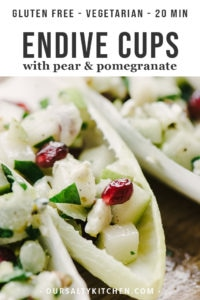 Cocktail appetizer endive cups stuffed with pears, pomegranate, and blue cheese.