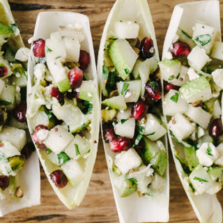 These endive cups are a fast, easy, and healthy holiday party appetizer. They're naturally vegetarian and gluten free, and bursting with flavor. The beautiful green hues and pops of red are seasonal and cheerful. Yum! #glutenfree #vegetarian #appetizer #holidayparty #christmasrecipe #winterrecipe