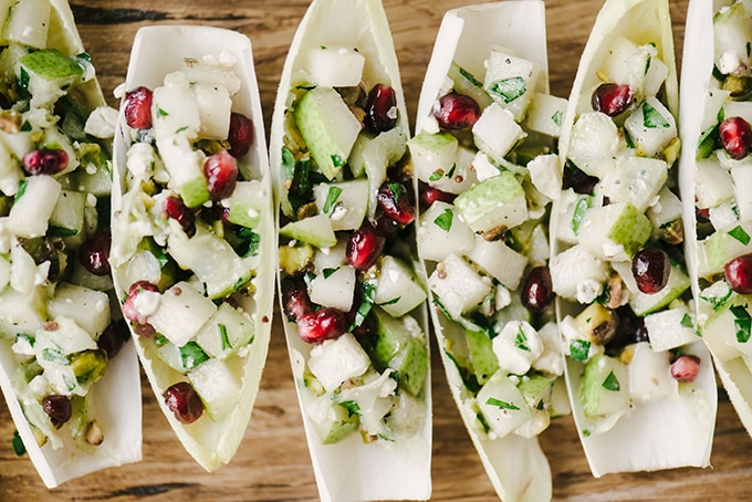 Six stuffed endive cup appetizers stuffed with pear, pomegranate, and blue cheese on a wood serving platter.