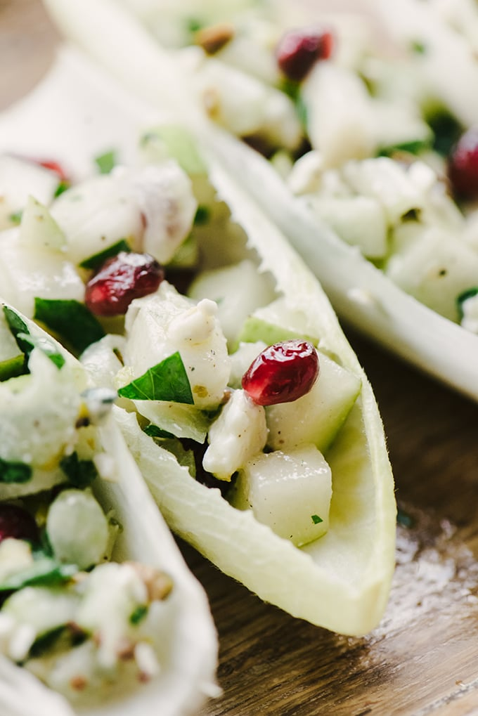 A detail image of an endive cup appetizer filled with pears, blue cheese, and pomegranate stuffing.