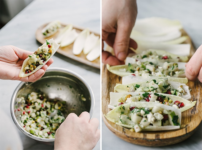 Left - a woman holding an endive cup, spooning in filling. Right - a woman's hand arranging stuffed endive appetizer cups on a wood serving board.