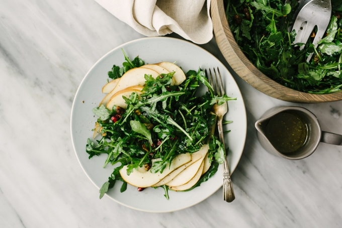 A large wood bowl and an individual serving of arugula pear salad on a marble table.