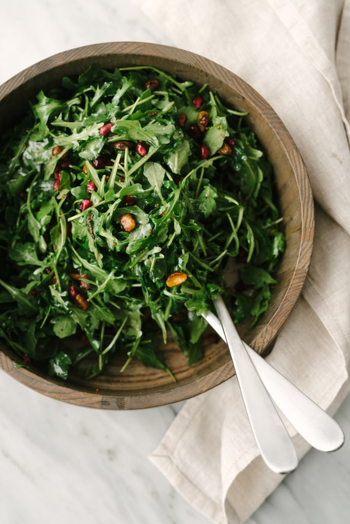 How to make whole30 and vegan arugula pear salad. Start with a base of baby arugula, roasted salted pistachios, and pomegranate seeds tossed in a salad bowl.