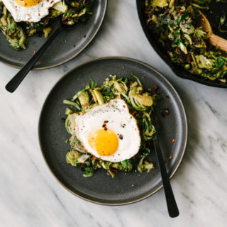Two plates of brussels sprouts hash with bacon topped with a fried egg on a marble table.