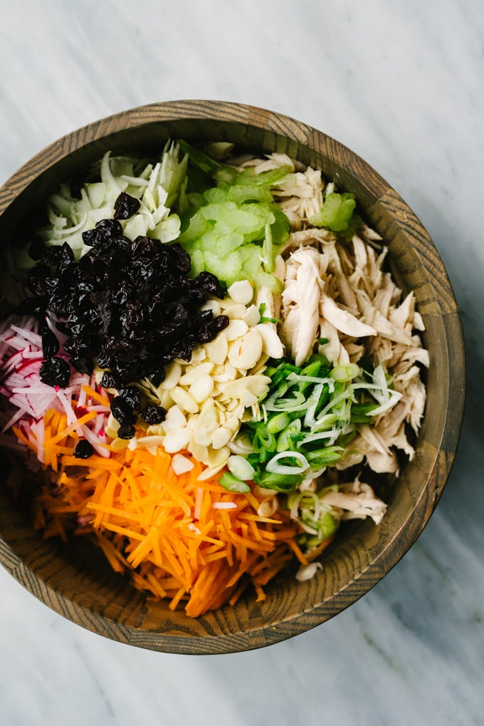 A wood bowl filled with the ingredients for whole30 chicken salad wrap stuffing - roasted chicken, carrots, cucumber, fennel, celery, green onions, dried cherries, and slivered almonds.