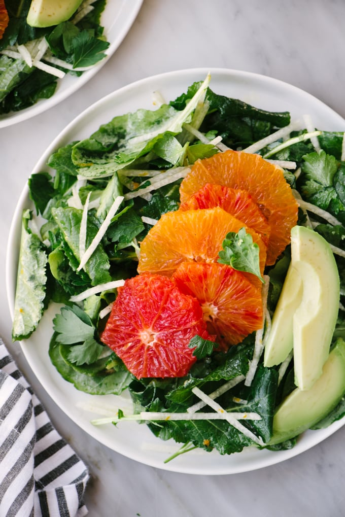 Baby kale and citrus salad on a white plate with jicama and avocado.