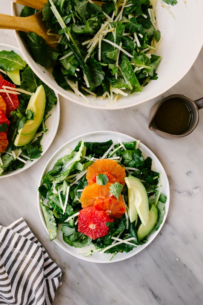 Two plates of kale citrus salad on a marble table with jicama and avocado.