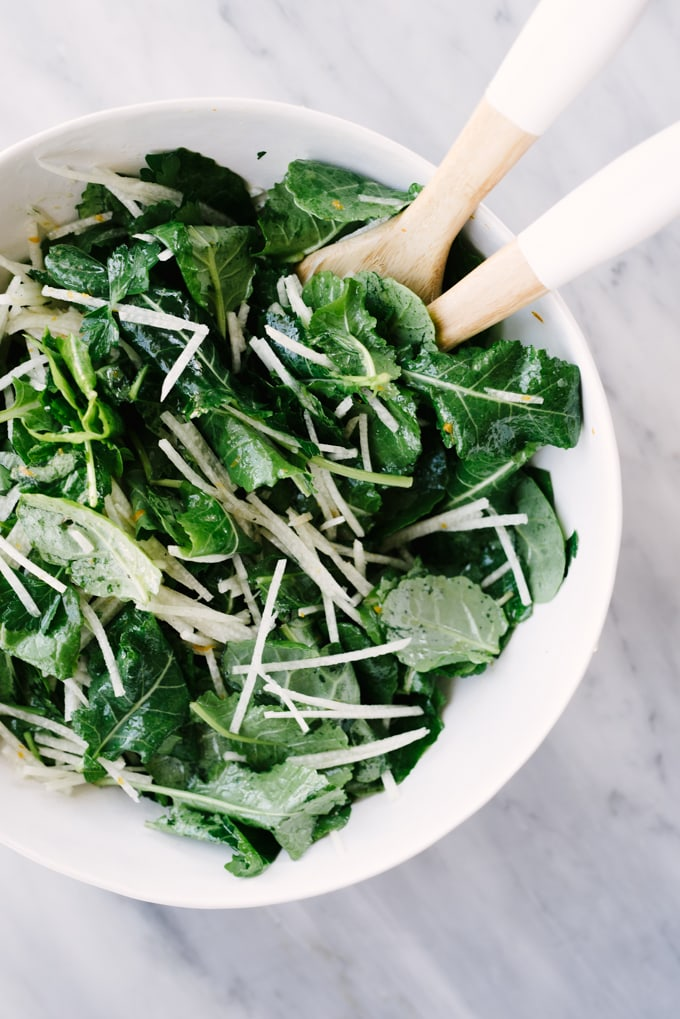 Baby kale and julienned jicama in a salad bowl, tossed with citrus vinaigrette.