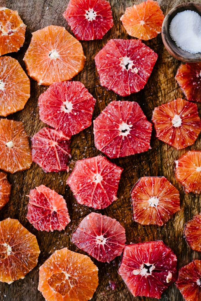 Slices of colorful winter citrus on a cutting board sprinkled with salt. Salted citrus is sweet and less bitter.