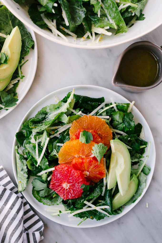 A plate of paleo citrus kale salad with multi-colored oranges, jicama, and avocado slices on a marble table.