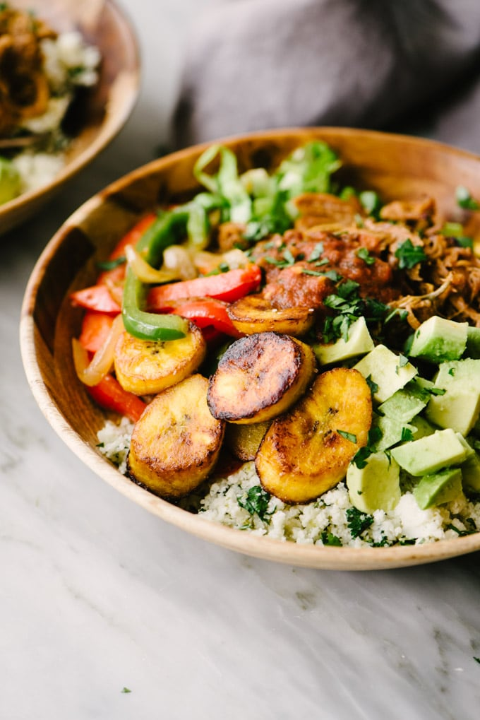 A wood bowl filled with a paleo burrito bowl! Pulled pork, fried plantains, sautéed peppers, and diced avocado over cilantro lime cauliflower rice.