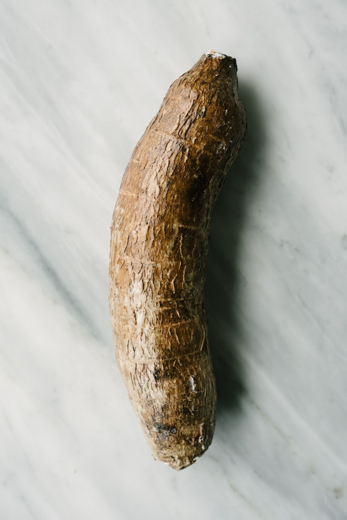 How to prepare garlic mashed yucca root, a paleo and whole30 side dish. Image of a whole yucca root on a marble background.