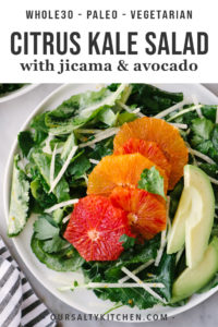A plate of kale citrus salad with jicama and avocado on a marble table.