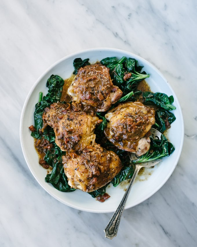 A platter of crispy and cream sun dried tomato tomato chicken thighs over a bed of wilted spinach on a marble table.