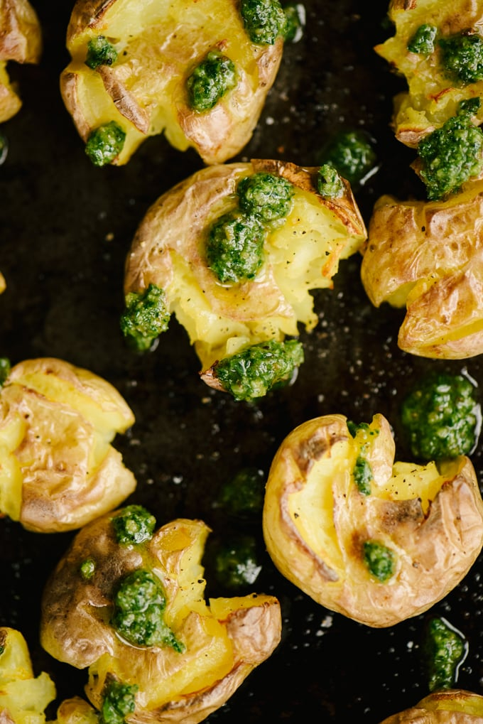 An overhead view of crispy smashed potatoes on a baking sheet drizzled with paleo pesto.