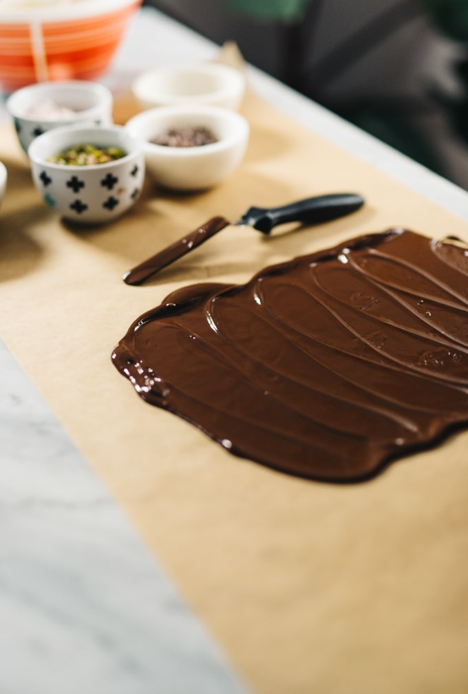 How to make homemade chocolate bark. Start by tempering the chocolate. Dark chocolate spread onto parchment paper with bowls of toppings in the background.