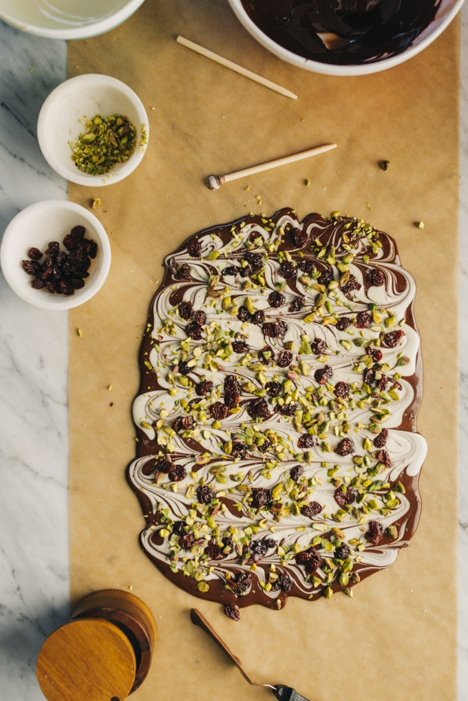 White and dark chocolate bark drying on a piece of parchment paper topped with dried cherries and pistachios.