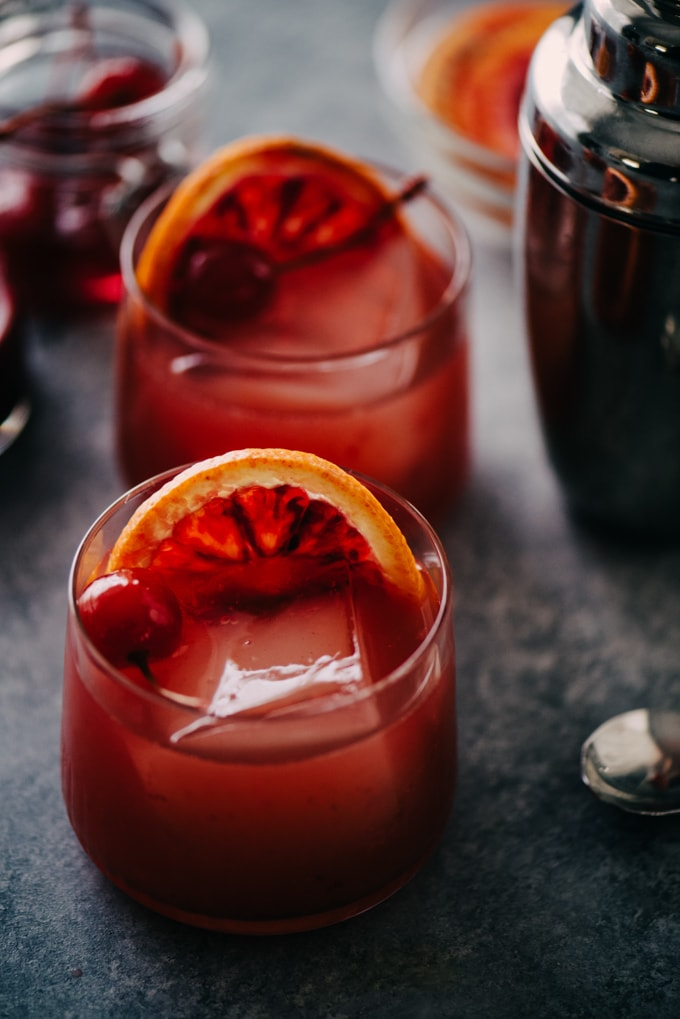 Two bourbon sour blood orange cocktails on a cement background with a cocktail shaker and maraschino cherries in the background.