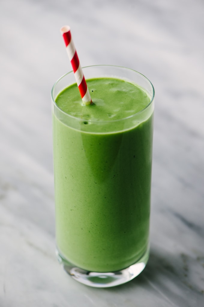 A green smoothie made with mango, spinach, yogurt, banana, and honey in a tall glass with a red and white straw on a marble background.
