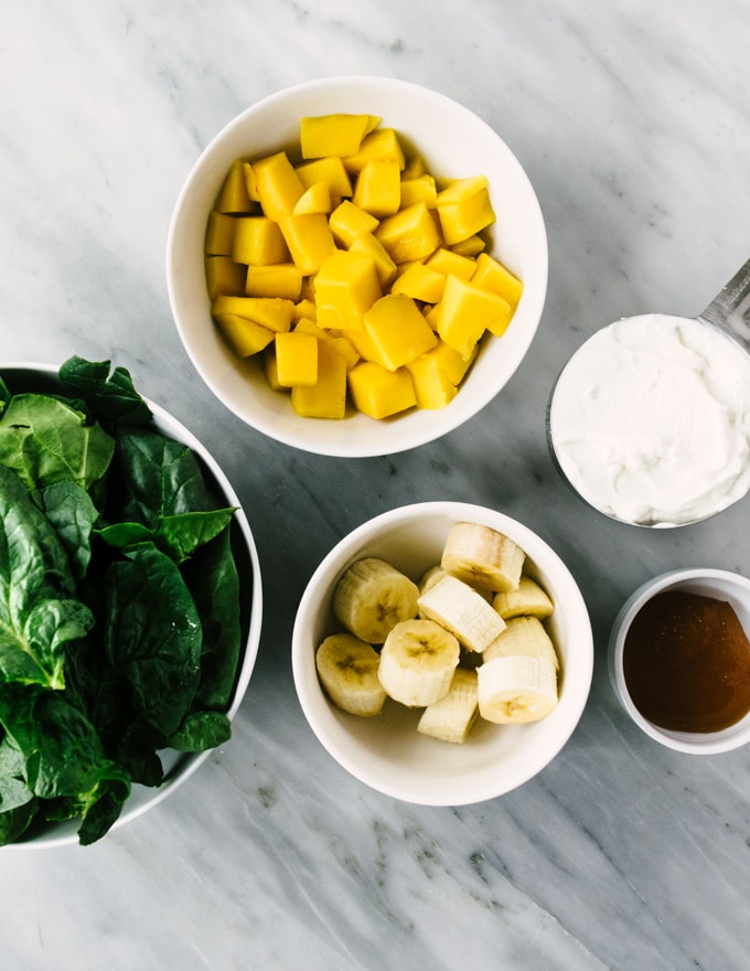 How to make my favorite mango spinach smoothie! Small bowls of diced mango, mature spinach, sliced banana, Siggi's yogurt, and raw honey on a marble background.