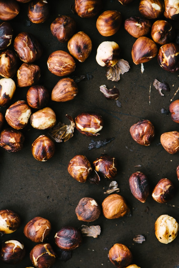 How to make toasted hazelnut vinaigrette. A close-up image of whole toasted hazelnuts in a saute pan.