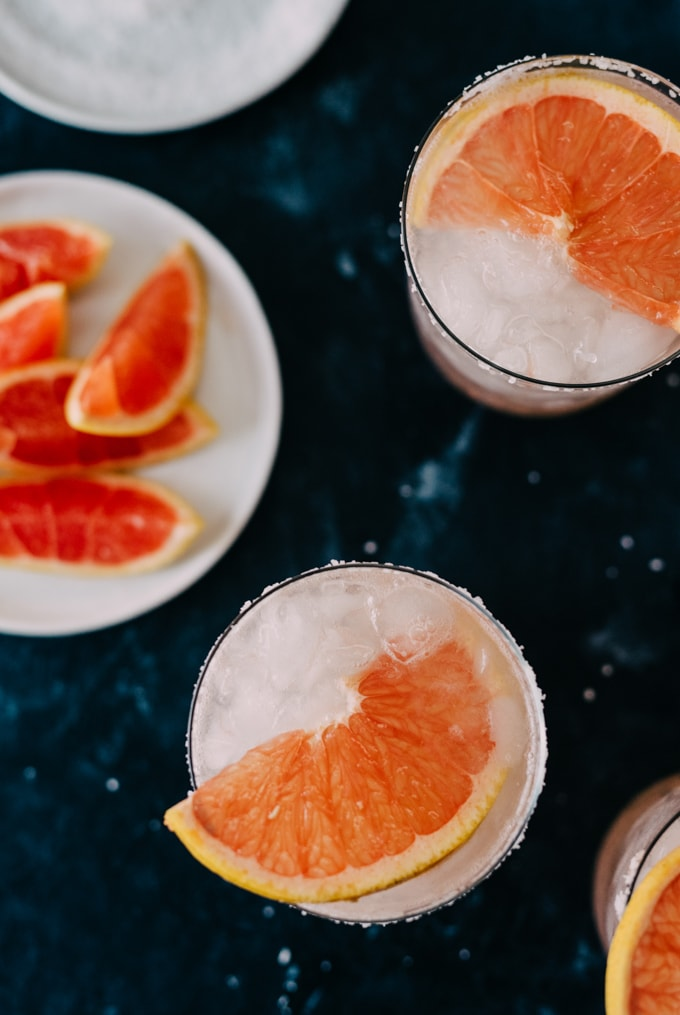 An overhead image of two paloma cocktails with fresh grapefruit slices and a small plate of grapefruit wedges on a black background.