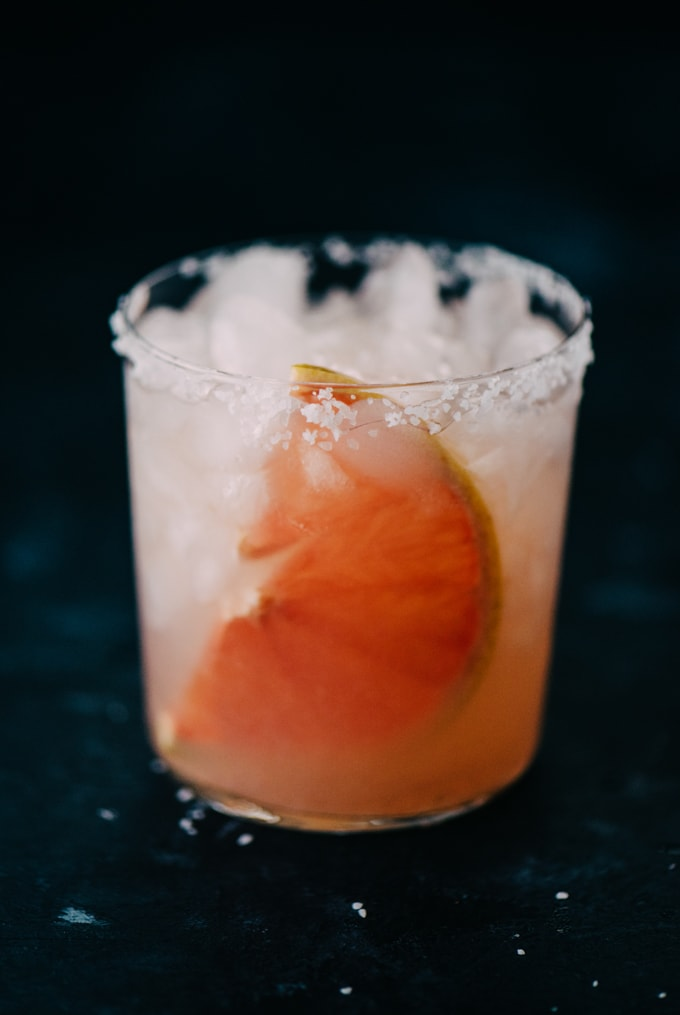 A close-up image of a freshly made paloma cocktail with fresh squeezed grapefruit juice on a black background.