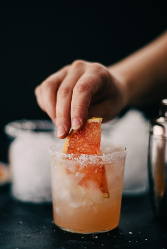 A woman placing a large slice of fresh grapefruit into a glass with a salted rim, filled with a refreshing pink paloma cocktail.