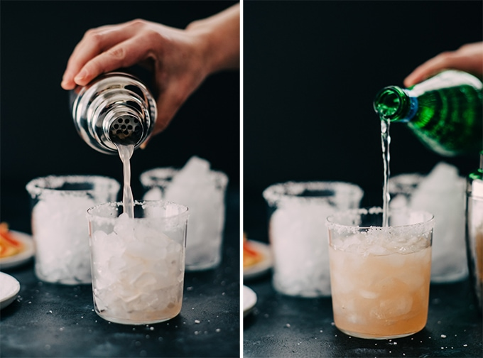 Left, a woman's hand pouring a paloma cocktail from a cocktail shaker into a glass with crushed ice and a salted rim. Left, topping the paloma cocktail with soda water.