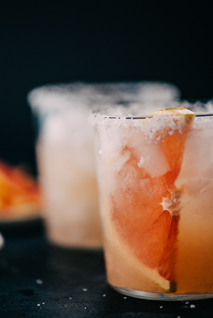A paloma cocktail in a glass with a salted rim and large slice of fresh grapefruit on a black surface.