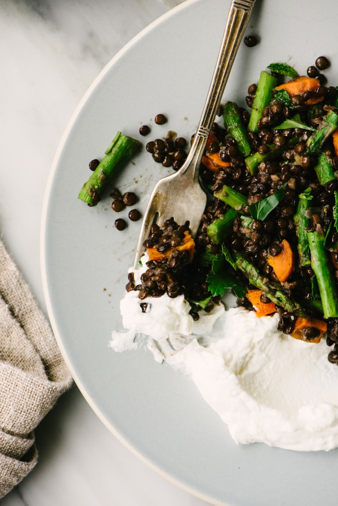 Black lentil salad with roasted asparagus and carrots with a side of greek yogurt garnish on a blue plate with a vintage fork.