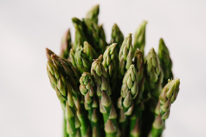 How to buy and store fresh asparagus. A close-up image of fresh asparagus tips with tightly packed florets.