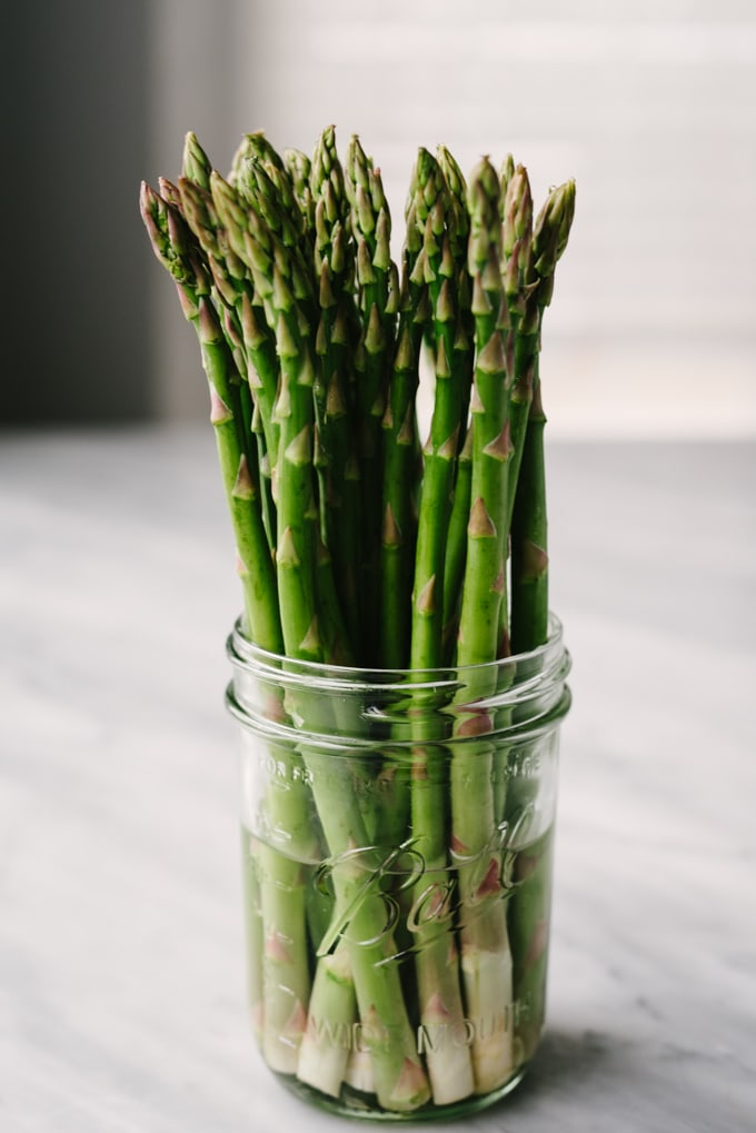 How to buy and store fresh asparagus. Fresh asparagus spears standing in a mason jar filled with cold water.