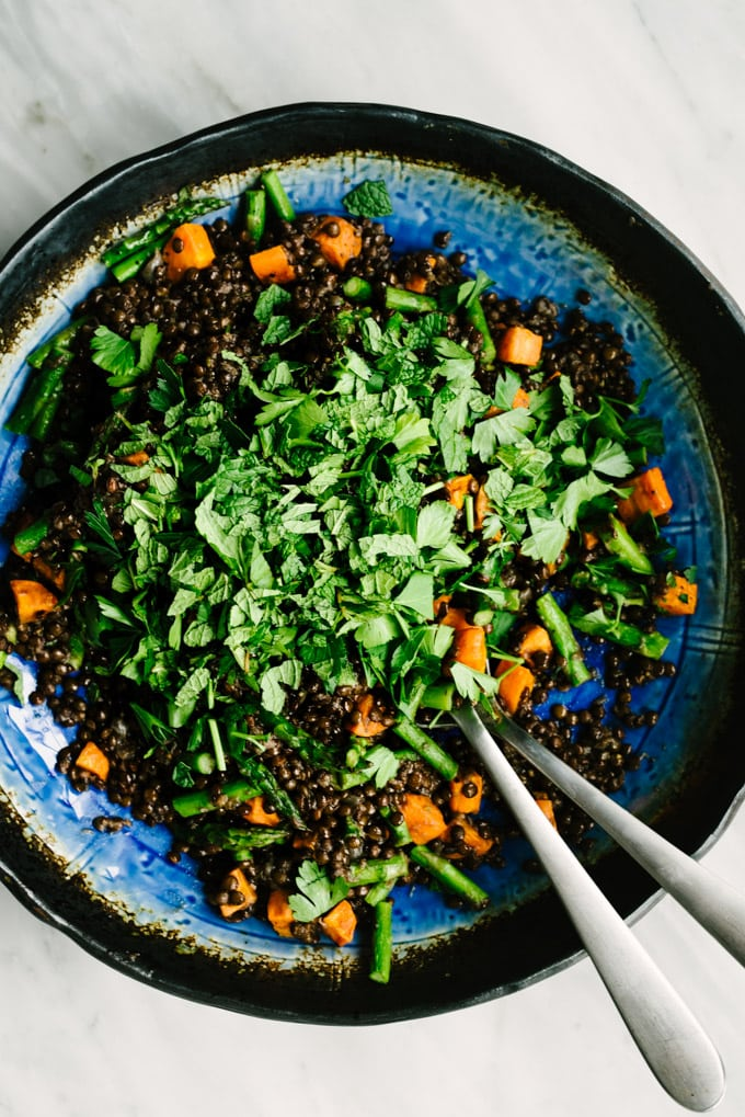 A large salad bowl filled with black lentils and roasted carrots and asparagus, topped with chopped fresh parsley and mint.