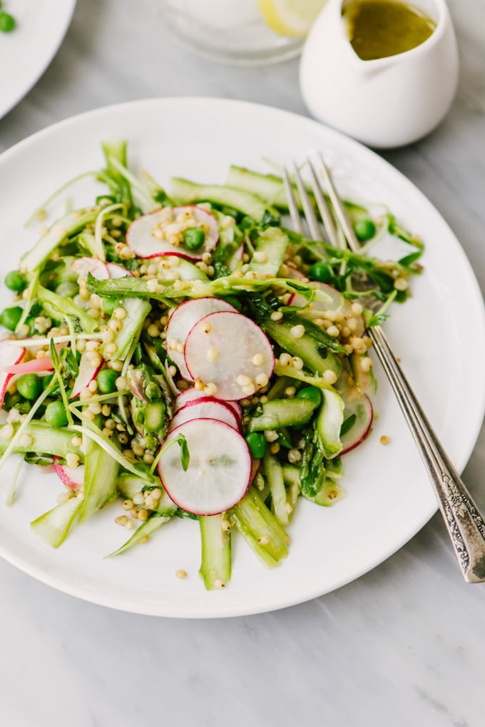 A white plate filled with spring sorghum salad with a fork and a small pitcher of lemon vinaigrette dressing on the side.