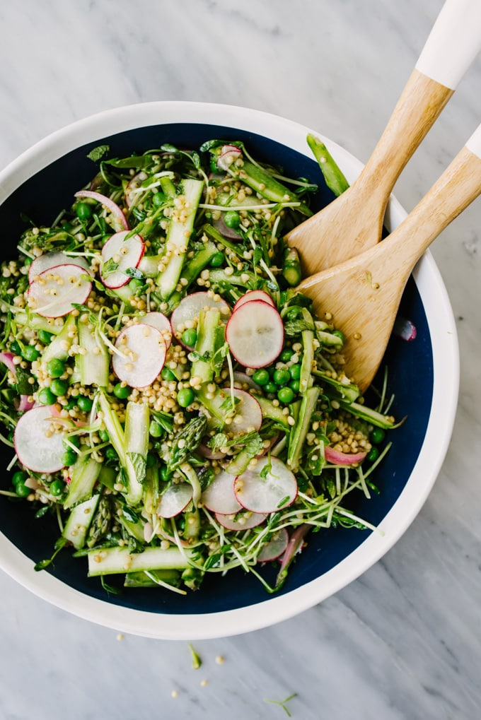 An overhead image of a blue and white bowl with wooden salad tongs filled with spring detox sorghum salad.