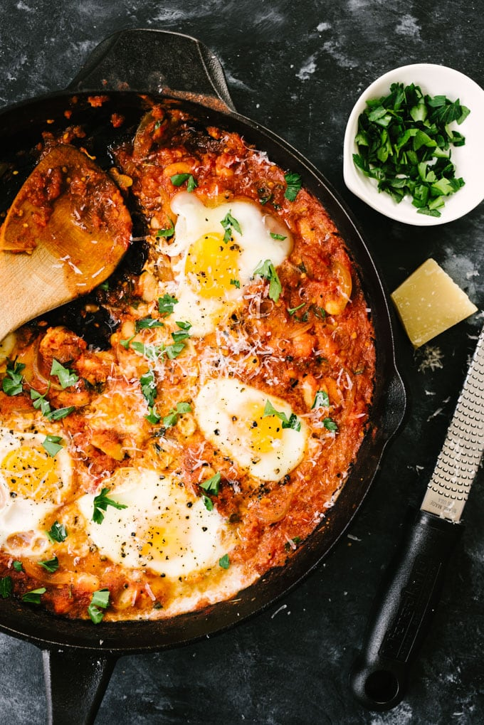 An overhead view of a cast iron skillet filled with eggs in purgatory with a single serving removed.