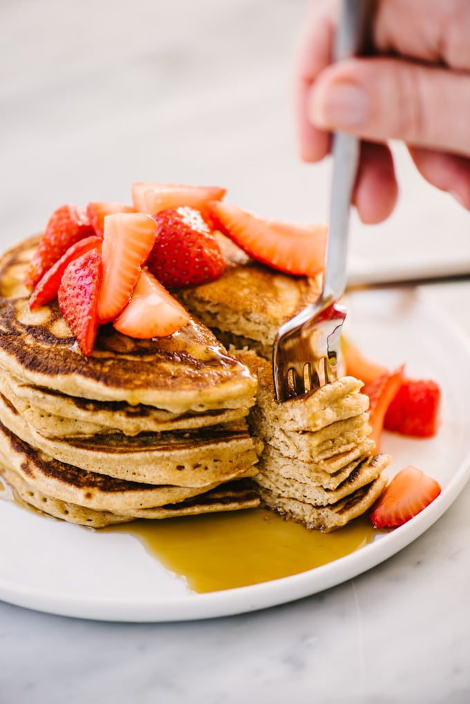 A woman holding a fork with a bite from a stack of whole grain pancakes topped with strawberries and real maple syrup.