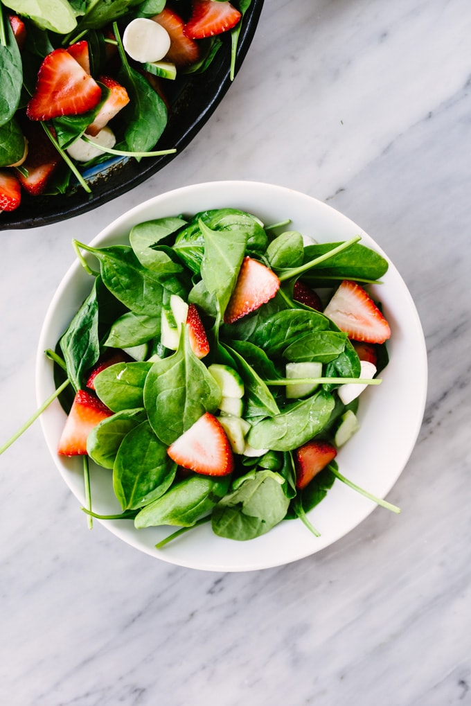 A tossed strawberry and spinach salad in a white bowl, ready to be topped with avocado and chicken.