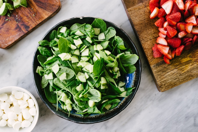A blue salad bowl filled with baby spinach, fresh basil leaves, and diced cucumber on a marble table. Sliced strawberries, fresh mozzarella, and diced avocados are on cutting boards surrounding the bowl.